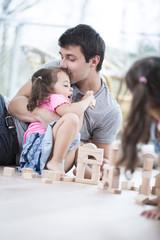 Loving father kissing daughter building blocks on floor