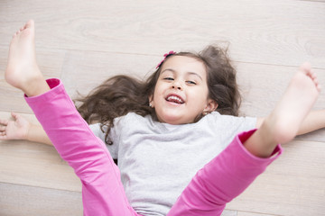 High angle view of playful girl lying on floor with legs raised at home