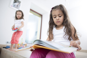 Cute girl reading book with sister playing in background at home