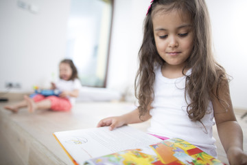 Cute girl reading book with sister in background at home