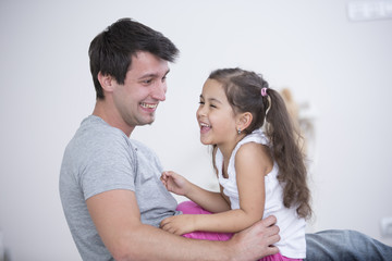 Side view of playful father and daughter at home