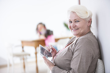 Portrait of happy senior woman using digital tablet with stylus at home