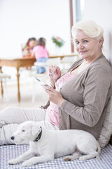 Portrait of happy senior woman using digital tablet by dog at home