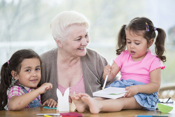 Happy senior woman with granddaughters making handicraft at home