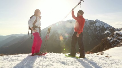 Hiker reaches mountain top, high five to companion