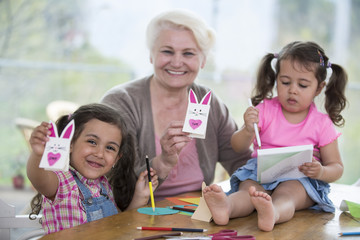 Portrait of happy senior woman showing craft rabbit while sitting with granddaughters at home