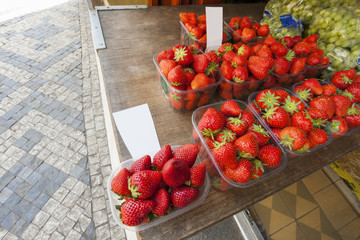 Fresh strawberries and grapes at outdoor market