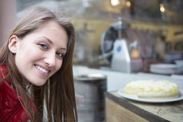 Portrait of happy woman by display cabinet in cafe