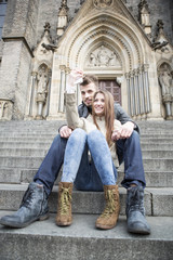 Full length of young couple taking selfie while sitting on steps outdoors