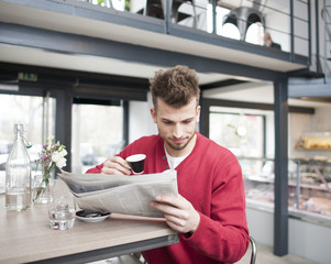 Young man reading newspaper while drinking coffee in cafe
