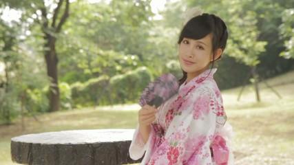 Asian woman in kimono fanning herself in Japanese garden