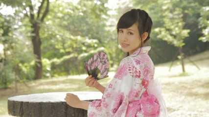 Asian woman in kimono fanning herself in Japanese garden
