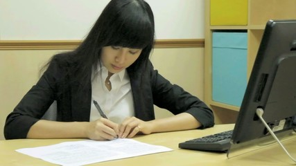 Chinese office lady writing at desk