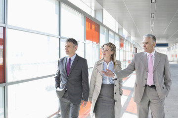Business colleagues walking on train platform