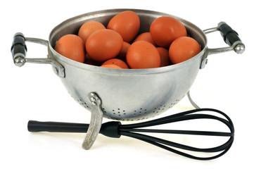 œufs dans une passoire et fouet de cuisine