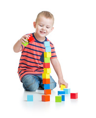 Kid playing and building high tower with colorful blocks
