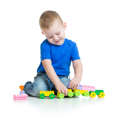 Kid boy playing with train toy sitting
