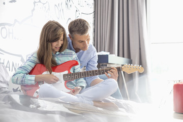 Father teaching daughter to play electric guitar at home