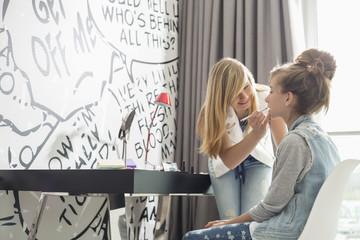 Teenage girl putting lipstick on sister at home