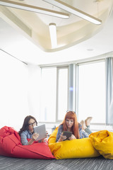 Businesswomen using digital tablets while relaxing on beanbag chairs in creative work space