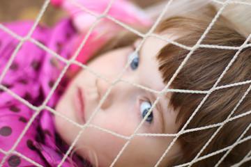 Littlt cute girl looks through white grid hammock