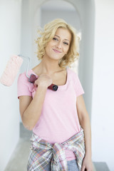 Portrait of beautiful woman holding paint roller in new house