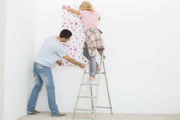 Full-length rear view of couple applying wallpaper to wall