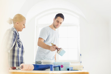 Mid-adult couple painting in new house