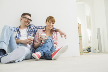 Full-length of cheerful couple with coffee cups in new house