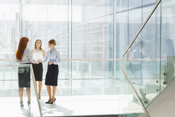 Full-length of businesswomen shaking hands in office