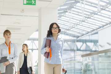 Smiling businesswomen with luggage and file walking at airport