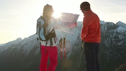 Hikers reaching mountain peak, looking at map