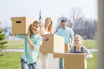 Family with cardboard boxes moving into new house