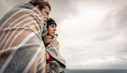 Young couple under blanket looking the sea in a cold day
