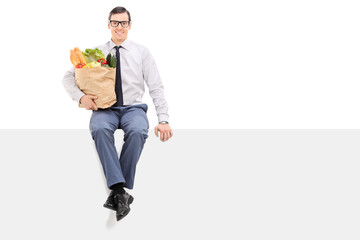 Man holding bag of groceries seated on panel