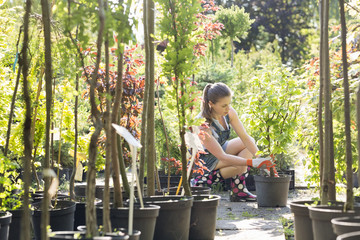 Woman planting pot at garden center