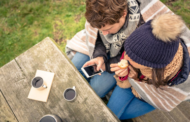 Young couple under blanket looking smartphone and eating muffin
