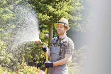 Happy man watering plants at garden