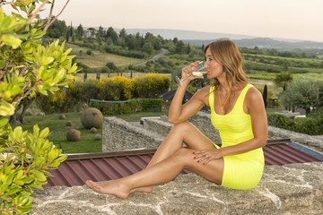 Happy young woman holding a glass of white wine