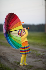 girl with rainbow umrella in the field