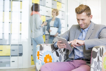 Businessman using tablet PC with colleagues discussing in background at creative office