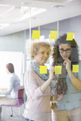 Businesswomen brainstorming with sticky notes in office