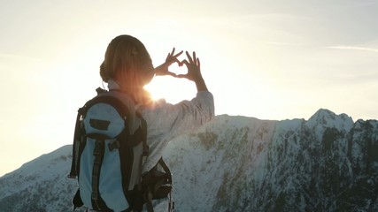 Hiker reaches mountain summit, makes heart shape with hands