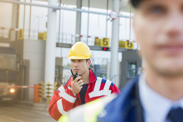 Male worker using walkie-talkie with colleague in foreground at shipyard