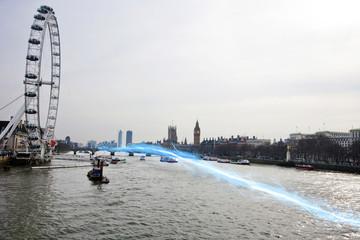 Blue streak of light passing over river Thames