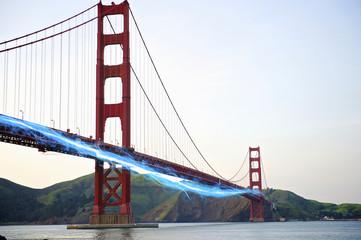 Blue streak of light passing by Golden Gate Bridge against clear sky