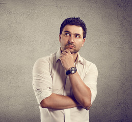 Close-up of young pensive businessman standing at the wall