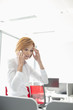 Shock businesswoman using cell phone in office