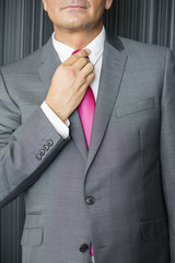 Midsection of mature businessman adjusting necktie