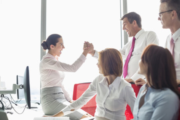 Businesspeople celebrating success in office